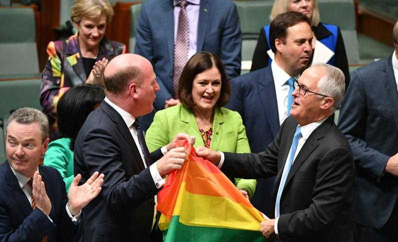Liberal Member for North Sydney Trent Zimmerman and Prime Minister Malcolm Turnbull celebrate the passing of the Marriage Amendment Bill in the House of Representatives at Parliament House in Canberra, Thursday, December 7, 2017.
