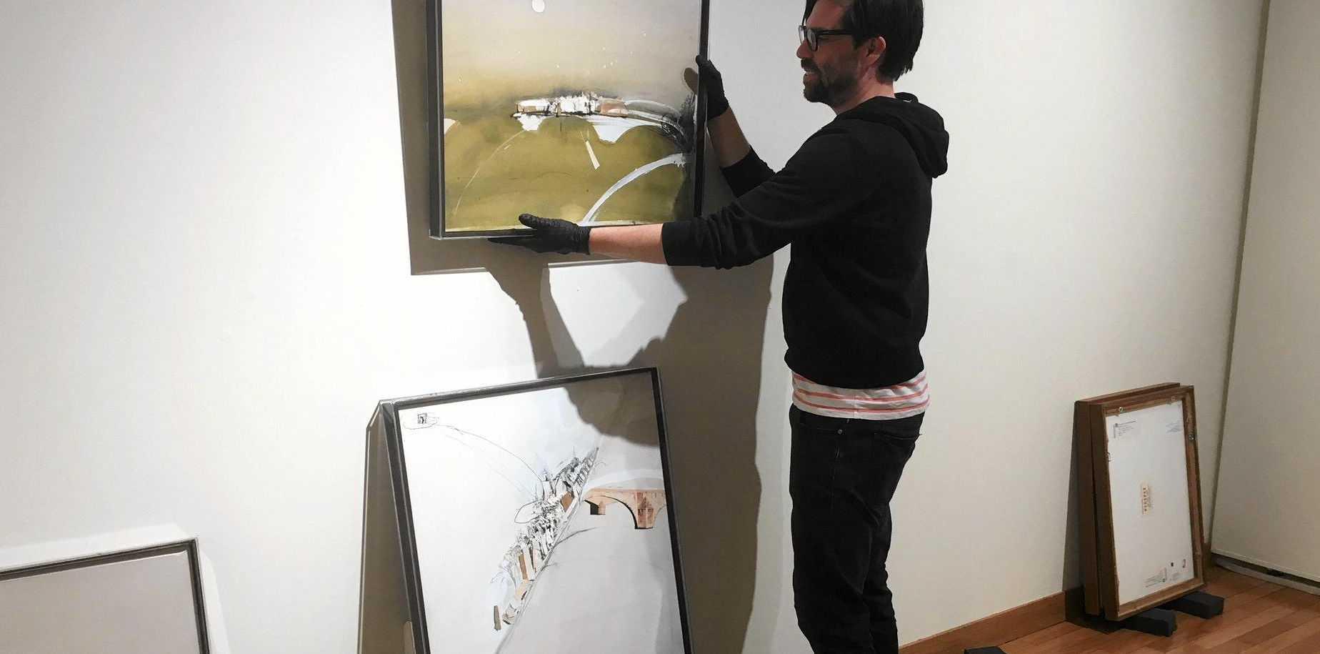 INSPIRING: Curator Josh White installs the Brett Whiteley exhibition at Gosford Regional Gallery.