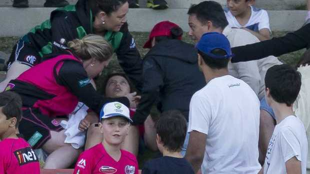The spectator is treated after being hit by an Ellyse Perry six at North Sydney Oval on Saturday night.