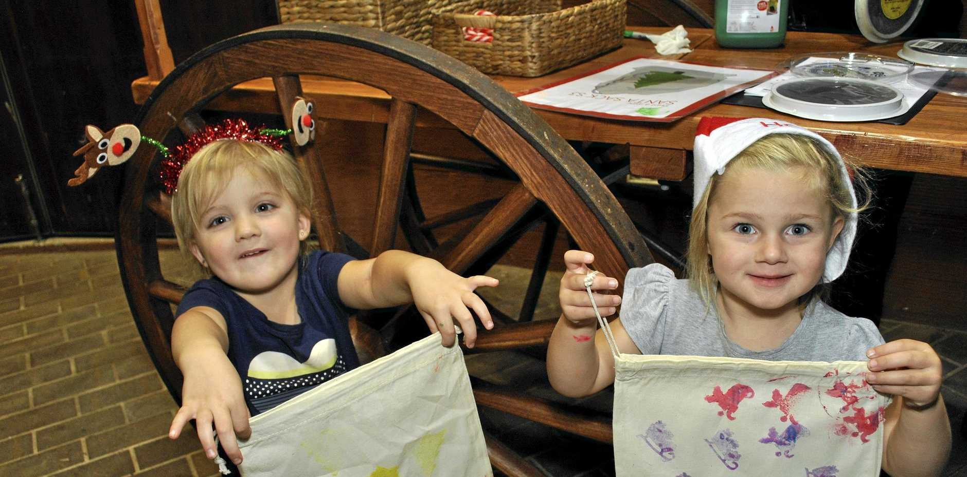 Caitlyn Malone (left) and Amity Cook proudly show off the Santa sacks they made .