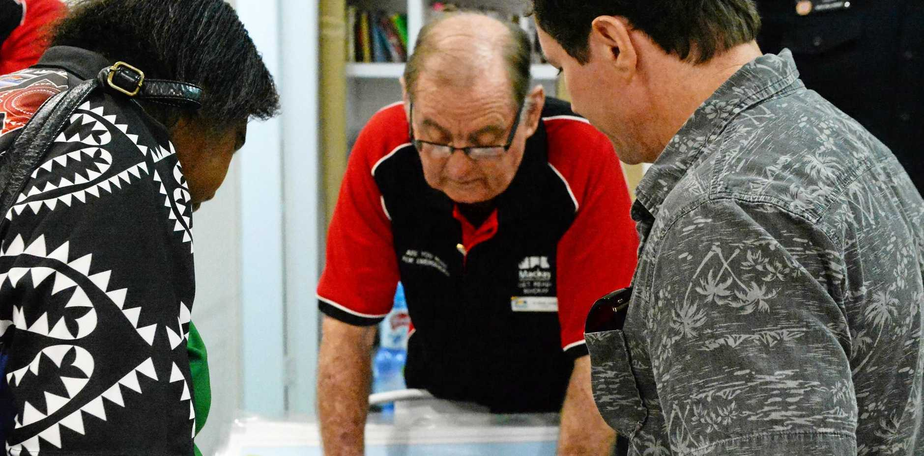 STORM SEASON: Melora Mataika and Mike Fry inspect flood inundation maps with Cr Kev Casey at Cyclone Saturday.
