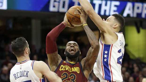 LeBron James shoots between Philadelphia 76ers' JJ Redick, left and Ben Simmons. (AP Photo/Tony Dejak)