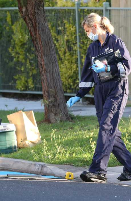 Another forensic officer examines the pole. Picture: David Crosling