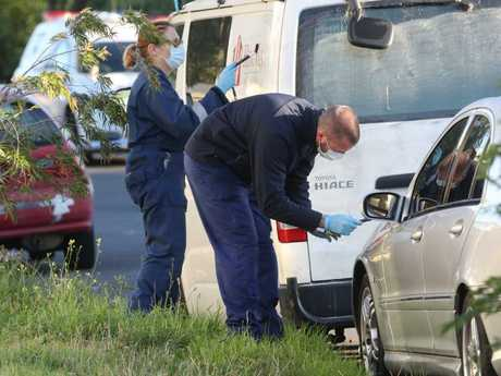 Police take evidence from cars parked in the street. Picture: David Crosling