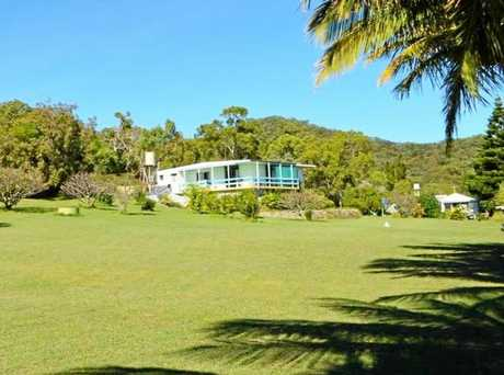 The cottage home has sweeping lawns and is a stroll to the beach.