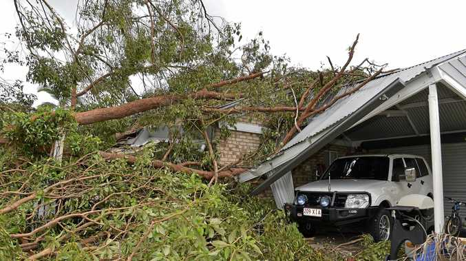 Residents of Beerwah clean up after a massive storm hit the area. A crushed carport in Sydney St.