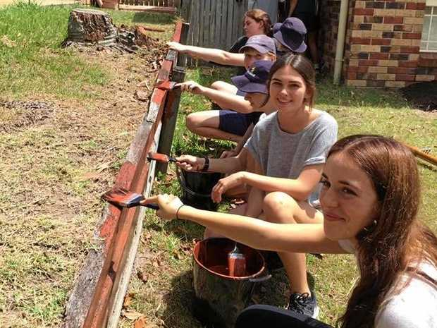 BRUSHES AT THE READY: Grammar students help with a garden clean-up as part of the school's Community Awareness Program.