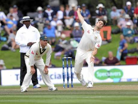Mitch Marsh bowls as Australian teammate David Warner watches on.