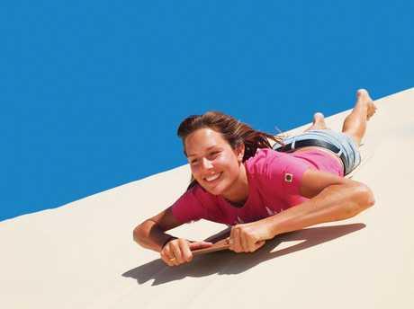 Take a ride down a sand dune on Moreton Island.