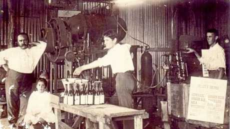 An interior photograph of Fernand Collet's softdrink factory. Fernand Collet is standing to the left presumably with his children. The photograph of his factory shows it was a fairly small family concern, of bush timber and corrugated iron construction with hand operated machinery.