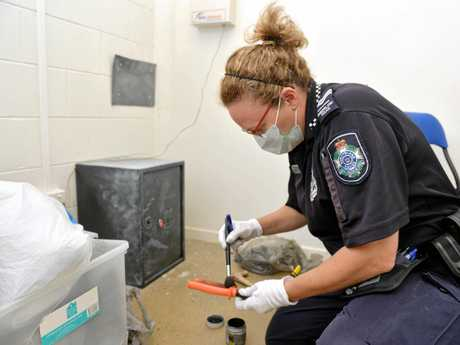 Senior Constable Yvonne Gaskell dusts for prints at the Salvation Army store at Bucasia.