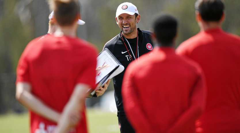 Tony Popovic talks to his players at a training session.