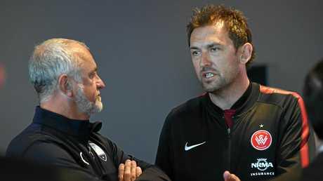 Graham Arnold (left) speaks with Tony Popovic.