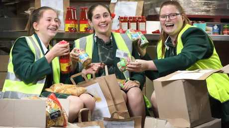 Westminster students Belle Hope, 15, Dayna Holroyd, 15, and Abigail Wicks, 15, at Foodbank where they volunteer to pack food hampers in Edwardstown, South Australia. Picture: AAP /Dean Martin