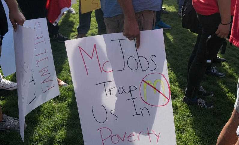 A protester holds a sign reading 'McJobs trap us in poverty' as hundreds of workers and supports took to the streets in Phoenix, Arizona on April 14, 2016 to call for a national minimum wage increase to an hour.