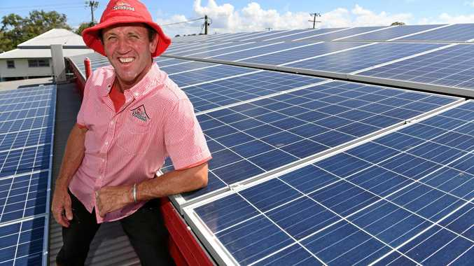 SOLAR SAVERS: Tony Mills with his solar panels on the roof of The Red Shed.