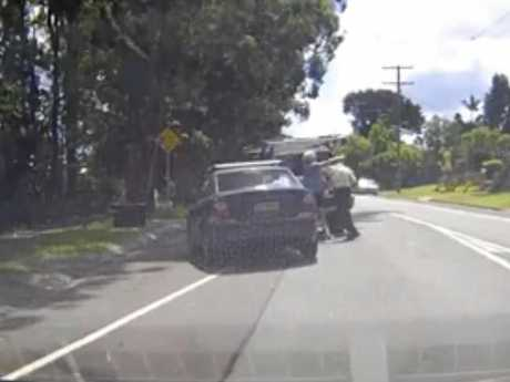 Two elderly men trade blows in the Glasshouse Mountains, halting traffic.