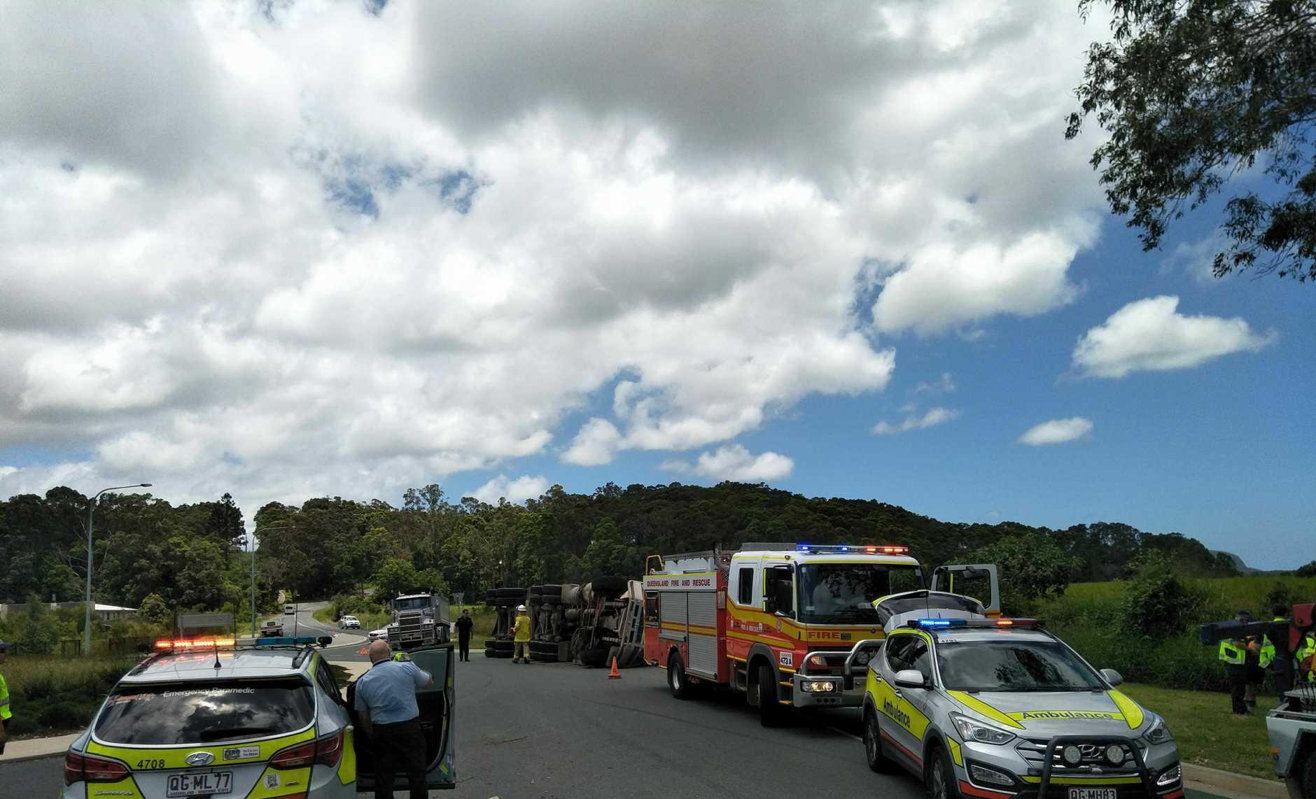 A SEMI-TRAILER has rolled at the entrance to a major Coast housing estate, with paramedics and police rushing to the crash.