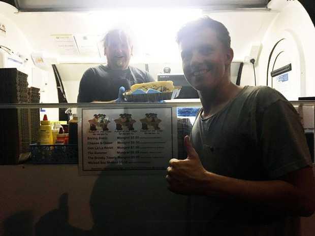 PARTY FEAST: Mongrel Hotdogs owner Rob Braddock serves customer Scott Burden outside Smokenleather.