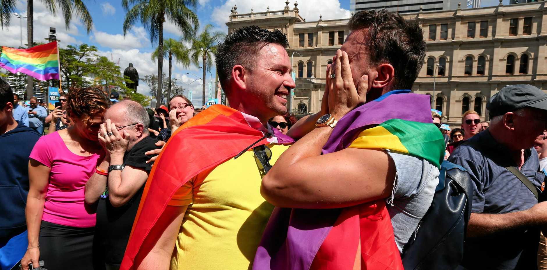 Scott D'Amico (left) and Brad Harker celebrate after the same sex marriage vote result announcement in Queens Park, Brisbane Australia, November 15, 2017. Australians have given same-sex marriage their approval with a 61.6 per cent 'yes' vote in a voluntary survey. (AAP Image/David Clark) NO ARCHIVING