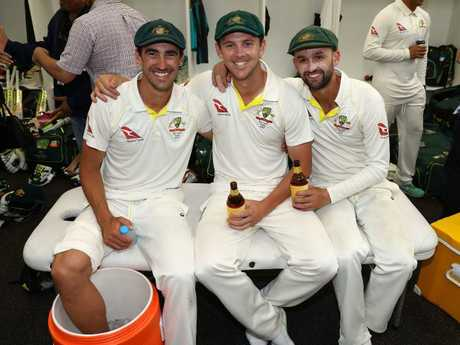 Mitchell Starc (left) rests his bruised heel in a bucket of ice as he celebrates with teammates Josh Hazlewood and Nathan Lyon on Monday night.