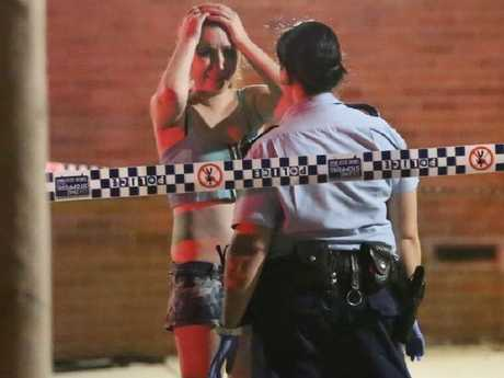 A woman speaks to police after the fatal shooting. Picture: Steve Tyson