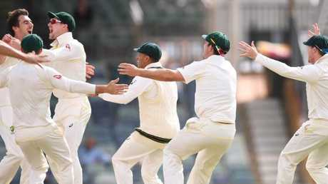 Australia players celebrate with Pat Cummins (left) after he took the wicket that wrapped up the third Test in Perth on Monday.