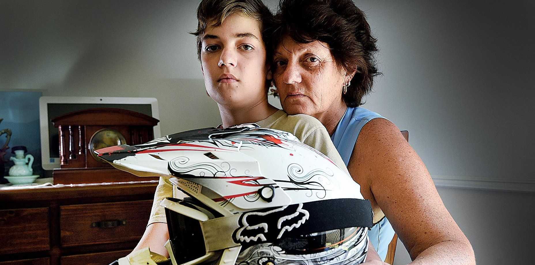 MISSING LINK: Diane Essery with son Nick, 13, holding his brother Matt's motorcycle helmet. Matt was killed in a crash in 2016.