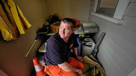 Acting Controller Ulmarra SES Dave Hardy sits in the doorway of their unit with a handy supply of sandbags, fresh water and tarpaulins for those who are coming for help in the rain event.