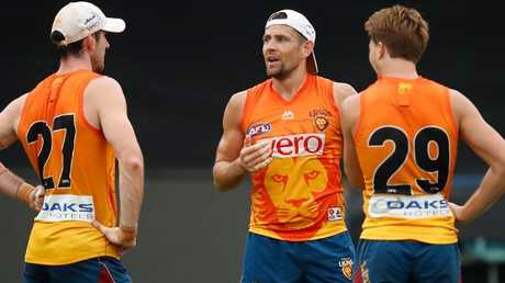 Luke Hodge chats with Lions teammates Darcy Gradiner and Alex Witherden. Picture: Getty Images