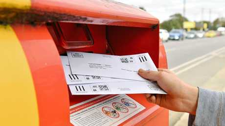 Sealed envelopes from the Marriage Law Postal Survey are seen being posted in Adelaide.