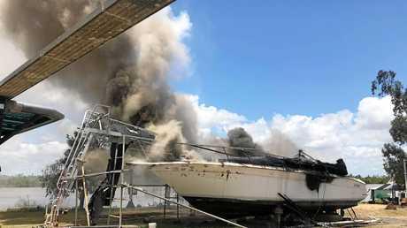 Firefighters battling a boat fire near the Nerimbera Boat Ramp.