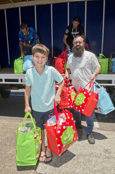 ( From left ) Adrian Young with Nat Spary from Base Services. 8 year old Adrian Young collected and made over 200 christmas hampers and delivered them to Base Services. Wednesday, 20th Dec, 2017.