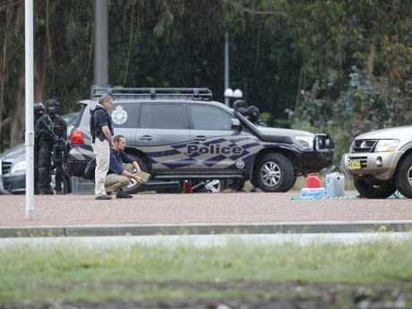Police negotiators talk to man who is beside Jerry cans of fuel on Anzac Parade in Canberra. Picture Gary Ramage