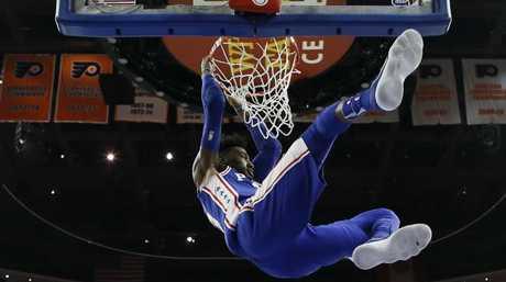Robert Covington hangs on the rim after a dunk. (AP Photo/Matt Slocum)