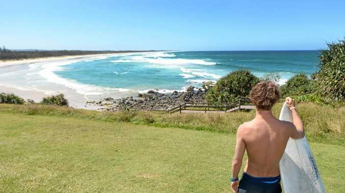 Local surfer Travis Coleman surveys the surfing waves at Cabarita Beach.