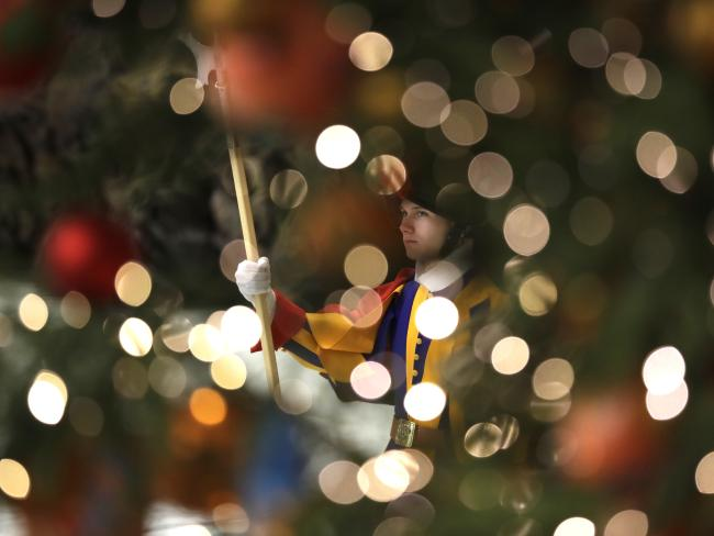 A Swiss guard is framed by Christmas tree lights as Pope Francis holds a general audience in the Paul VI Hall at the Vatican. Picture: AP