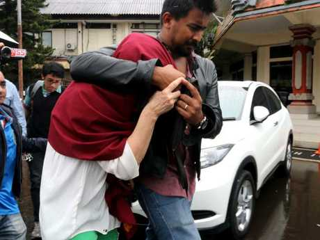 The mother of Isaac Emmanuel Roberts, with lawyer Yoga Cahyadi, leaves Bali's Police headquarters after meeting her son. Picture: Lukman Bintoro