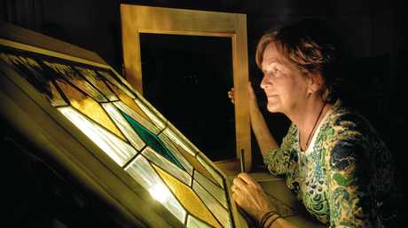 Jan Fletcher takes a close look at a stained glass window she is working from in a leadlight class at the New School of Arts Neighbourhood House. The house is offering free classes this week as part of Neighbourhood House week.
