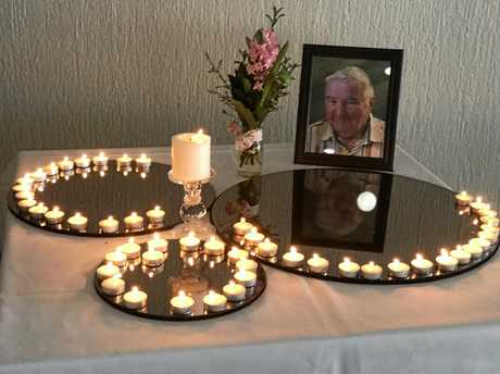 Candles lit by guests at a remembrance ceremony for organ donors surrounding an image of Rodney Webb.