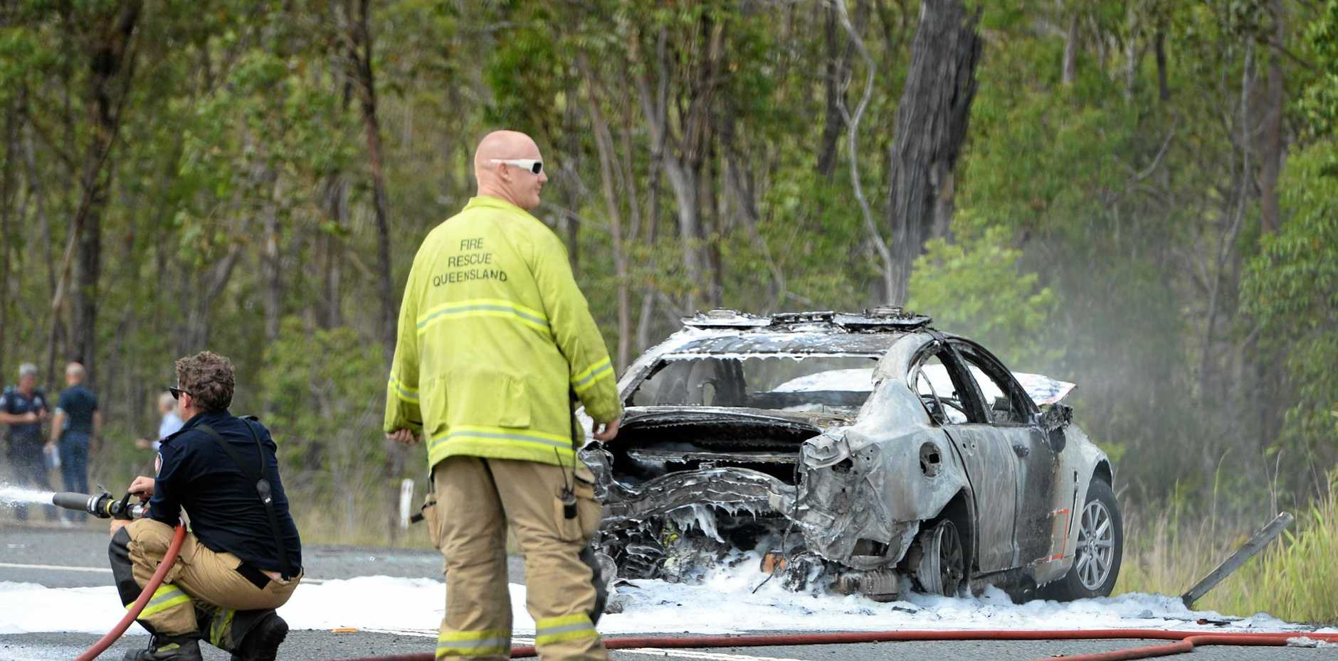 Emergency services respond to a crash between a police car and another car on Emu Park Road 1km west of the Coorooman Creek intersection.   A firefighter hoses down spilt fuel from the burned out police car.