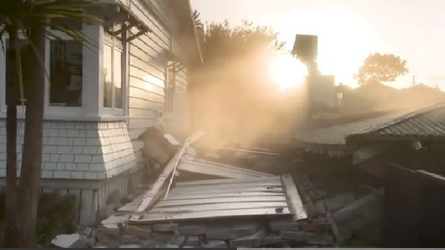 The moment a house in Auckland is damaged during the demolition of a neighbouring property.