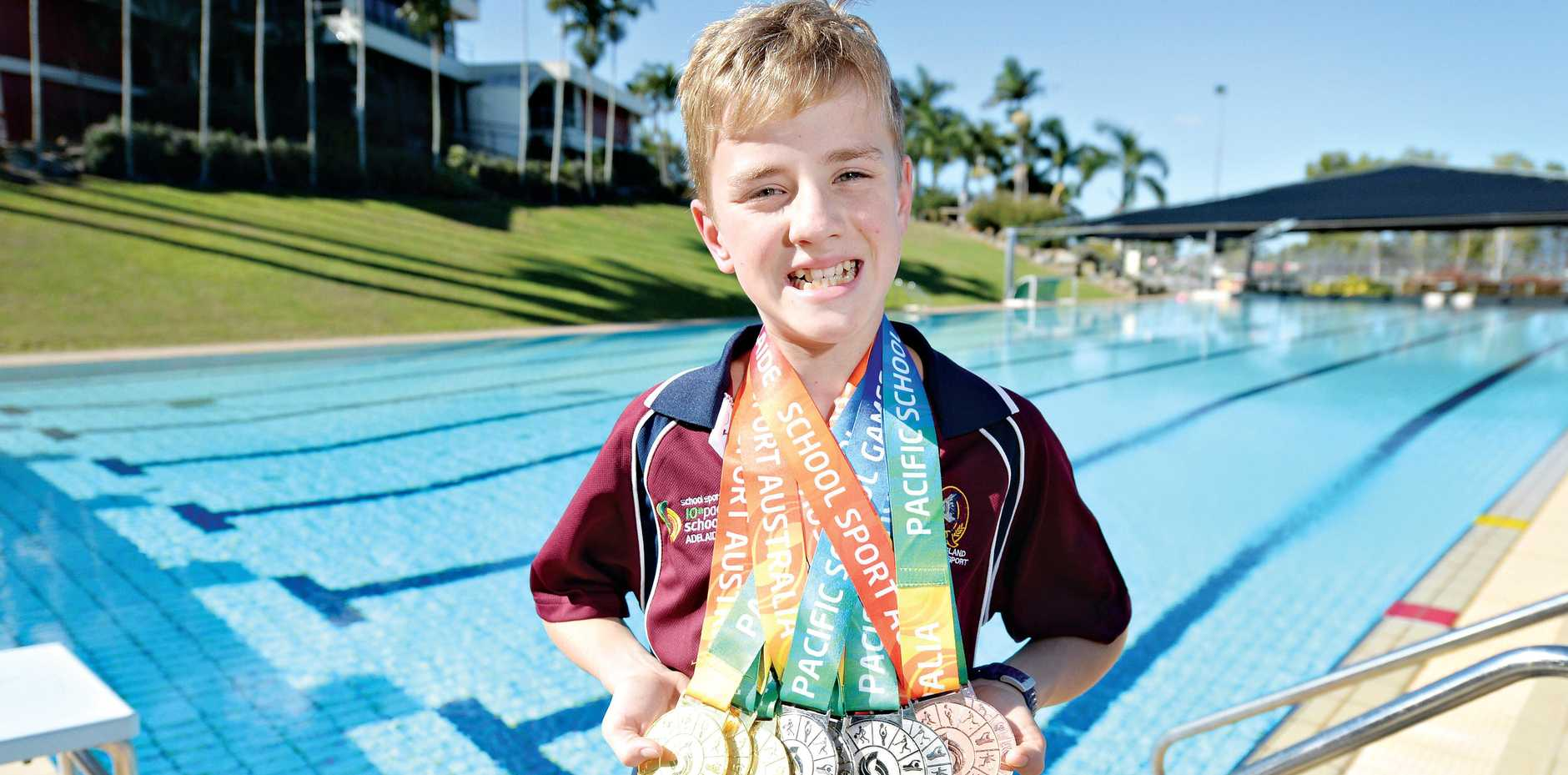 STARRING ROLE: Caribeae Swimming Club member Will Salmond with his nine-medal from the Pan Pacific Games.