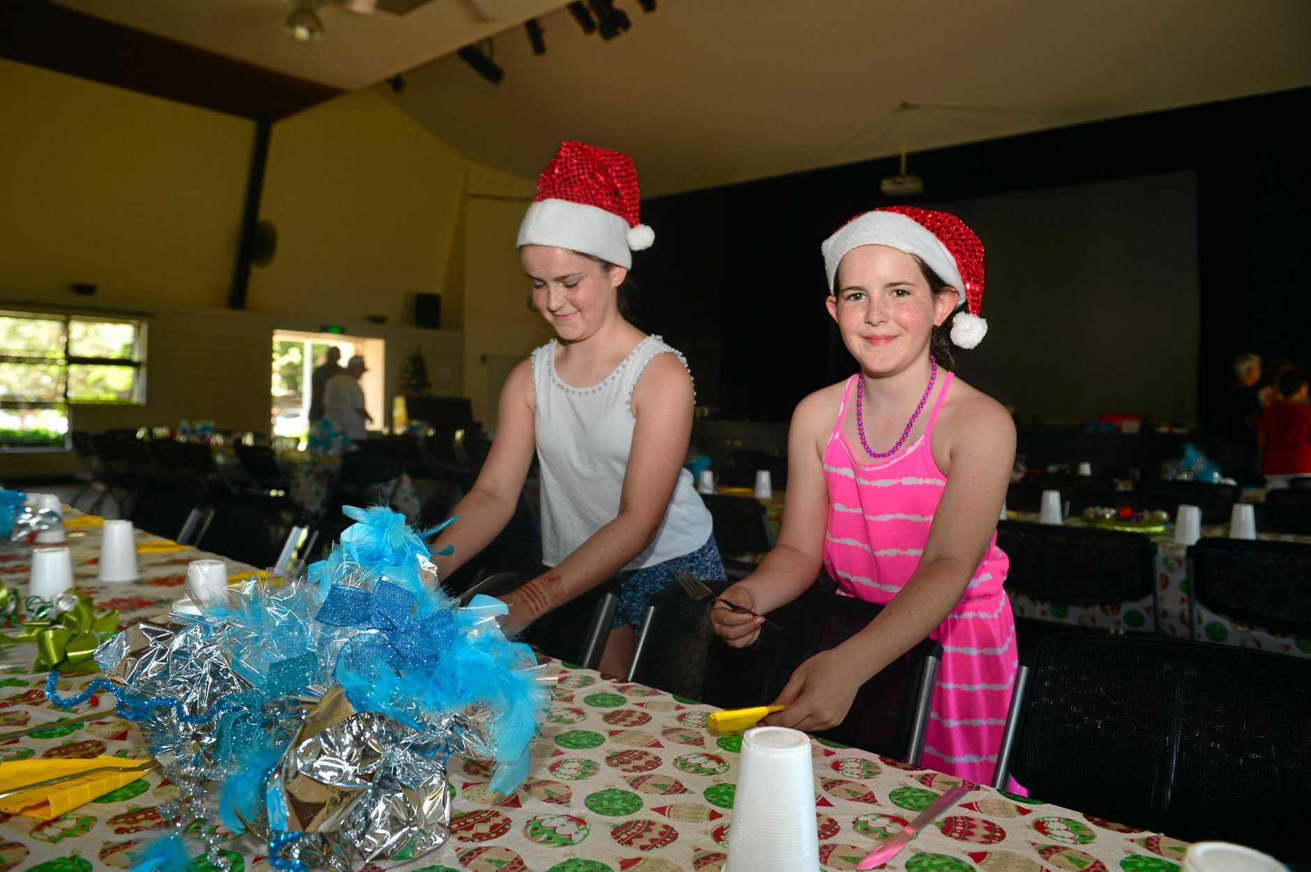 COMMUNITY SPIRIT: Isabella, 12 and Caitlin Barry, 9 have given up part of their Christmas Day to help set the tables that will seat 100 homeless people for Christmas luncheon.