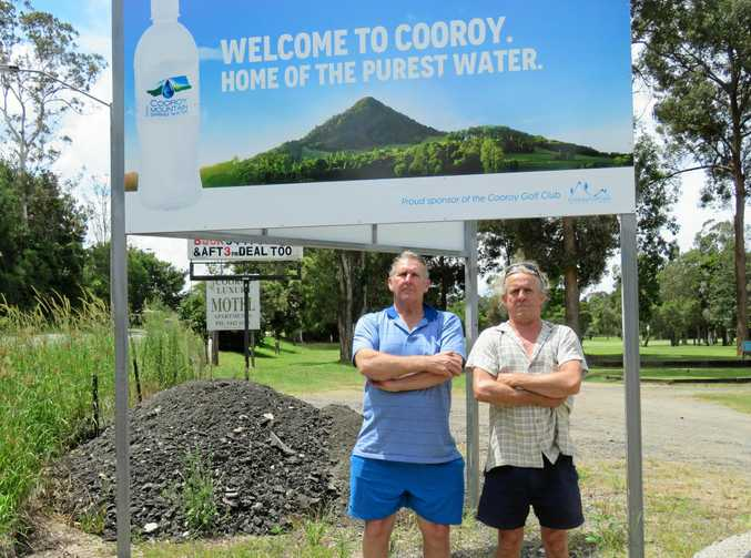 NOT HAPPY: Cooroy Golf Club players next to one of the illegal signs on club land.