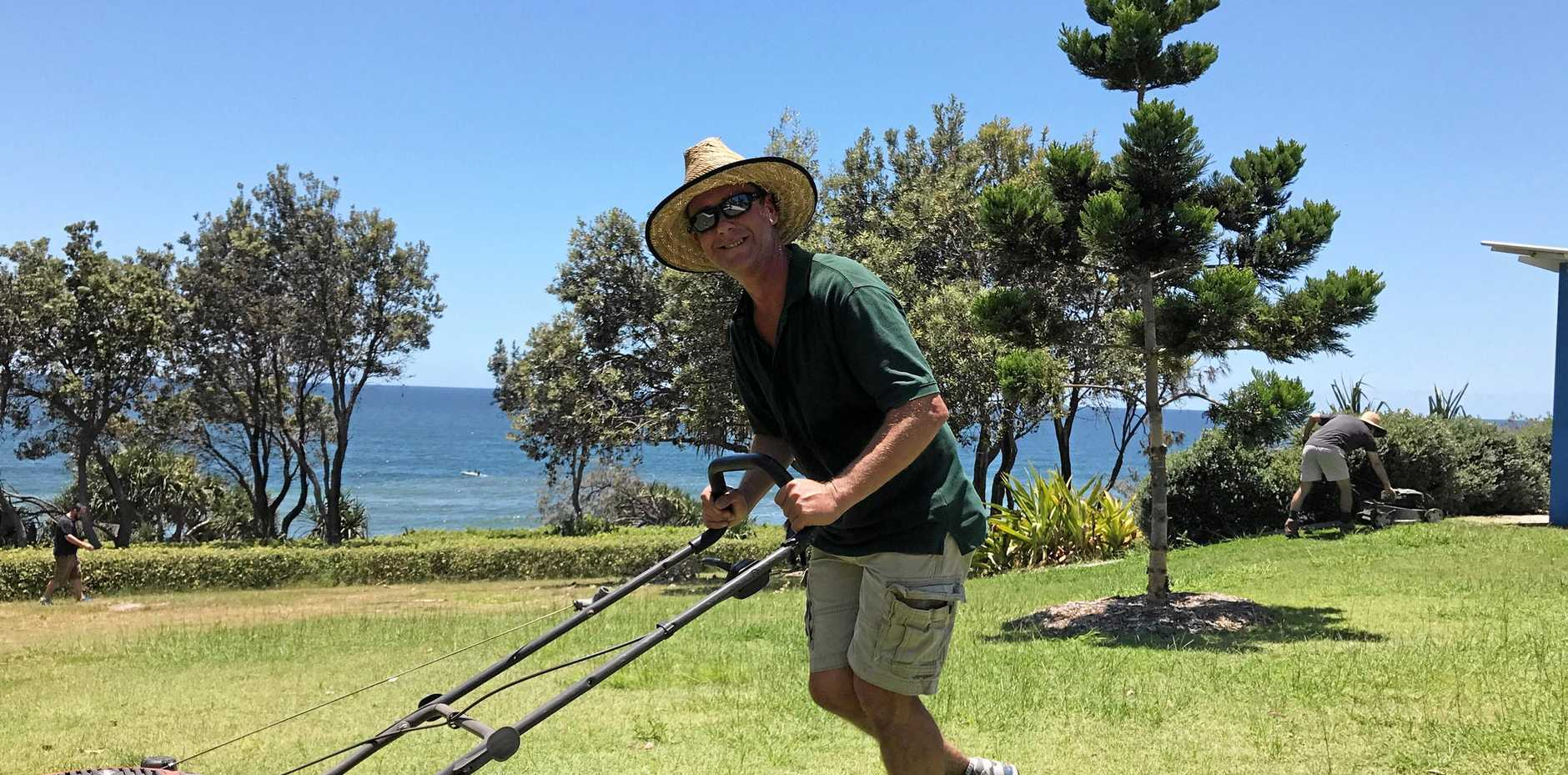 Rainbow Beach locals mow the public grounds after complaints from tourists.