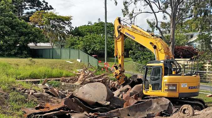 MOVING AHEAD: Crushing the old petrol tanks on the resort development site at Iluka.