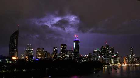 Storm clouds and lightning seen passing over the Brisbane skyline from the Kangaroo Point cliffs Tuesday evening. Picture: AAP/Darren England