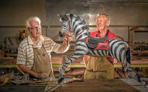 Grafton Men's Shed member Greg Ryan and Eddie Chapman look over Debra the Zebra, created to raise money for palliaitve care.