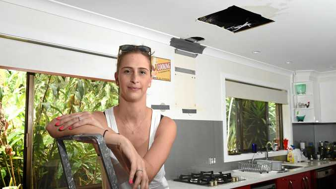 GRATEFUL: Candace Garam, of Sydney, in front of the section of roof in the Alstonville house where the fire started after lightning struck the roof during the Christmas Day storm.